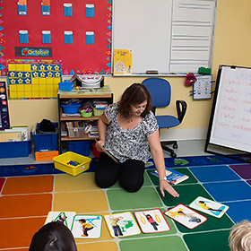 teacher on floor with teaching materials